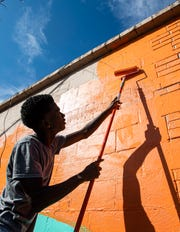 Carpenter Art Garden participant Terry Rogers paints a mural on the side of a building in Binghampton on Oct. 9, 2019.