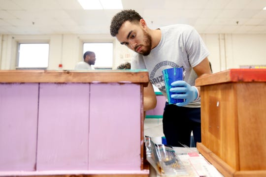The Grizzlies' Tyus Jones paints a planter while volunteering at Bethel Grove Elementary School in late October.