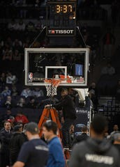 A worker inspects a rim, delaying the game between the Timberwolves and Bucks on Monday night in Minneapolis.