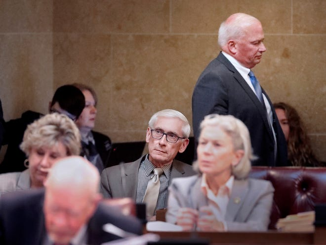 Wisconsin Gov. Tony Evers, seated at center, listens to a Senate debate regarding his pick to head the Department of Agriculture, Trade and Consumer Protection during a session at the Capitol in MadisonTuesday. Walking behind during the proceedings is Senate Majority Leader Scott Fitzgerald, R-Juneau.