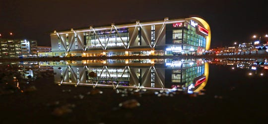The Fiserv Forum reflects in a puddle of water at the former site of the BMO Harris Bradley Center on Sunday, Nov. 3, 2019.
