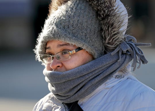 Jasmine Wooten of Milwaukee is bundled up from the cold while waiting for her bus at the corner of North Water Street and East Juneau Avenue in Milwaukee on Tuesday. After the 2to 4inches of expected snow falls Wednesday, the cold will set in. Lows Wednesday nightwill drop into the mid- to upper teens inland away from Lake Michigan. Highs Thursday and Friday probably won't get above freezing and will be close to 20 degrees below normal, according to the weather service.