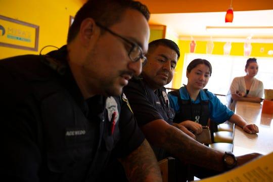 Community liaison officers Jose Acevedo, left, and Eliel Contreras order at Myra's Jugos y Frutas on Mitchell Street in Milwaukee.