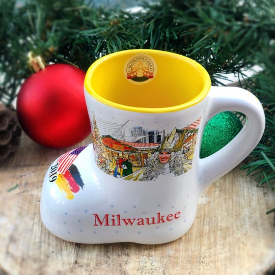The 2019 Milwaukee Christkindlmarket mug shows Fiserv Forum, the new Northwestern Mutual office tower and other Milwaukee buildings in the background of the market.