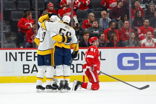 Nashville Predators center Matt Duchene (obscured) celebrates his goal with Filip Forsberg (9) and Roman Josi (59) as Detroit Red Wings center Frans Nielsen (81) kneels on the ice in the second period of an NHL hockey game Monday, Nov. 4, 2019, in Detroit.