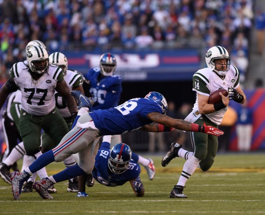 Jets QB Ryan Fitzpatrick tries to evade a tackle by Giants Damontre Moore in the second quarter.  MICHAEL KARAS / STAFF PHOTOGRAPHER