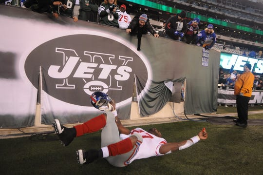 Giants' Brandon Jacobs pretends to crash while flying into the locker room after their win over the Jets at MetLife Stadium.