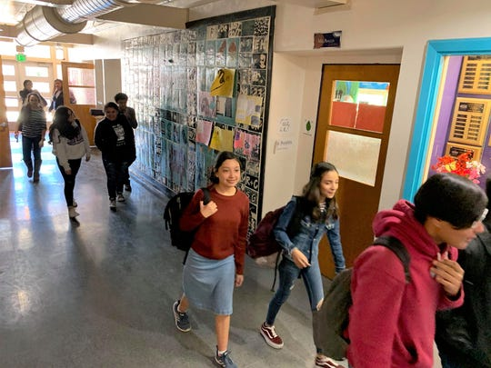 Students pass through the main hallway at La Academia Dolores Huerta charter middle school on Monday, Nov. 4, 2019.