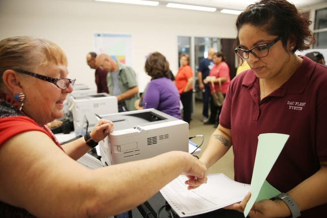 Cheryl Young, left, presiding judge at the Las Cruces City Hall polling place, shows voter Yvette Rodriguez her ballot, during the 2019 election on Tuesday Nov. 5, 2019.