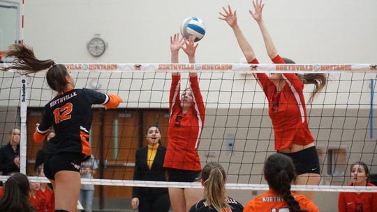 Northville High's Jenna Boksha, left, tries to get a spike past two Canton defenders.
