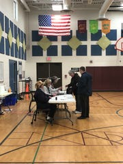 Ted and Betsy Lambert of Milford speak with election inspectors in precinct 2, the Johnson Elementary gym, before casting yes votes on two proposals for Huron Valley Schools.