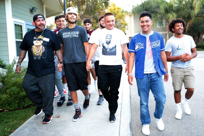 Izzy Ramirez, second from left, grips the hand of his brother Jessie Alvarez, left, and Joshua Davidson while walking with his Rancho Mirage High School friends and football teammates outside the Totally Kids Rehabilitation Hospital in Loma Linda, Calif., on Saturday, Nov. 2, 2019. Ramirez had a cerebral AVM rupture on Sept. 27, 2019.