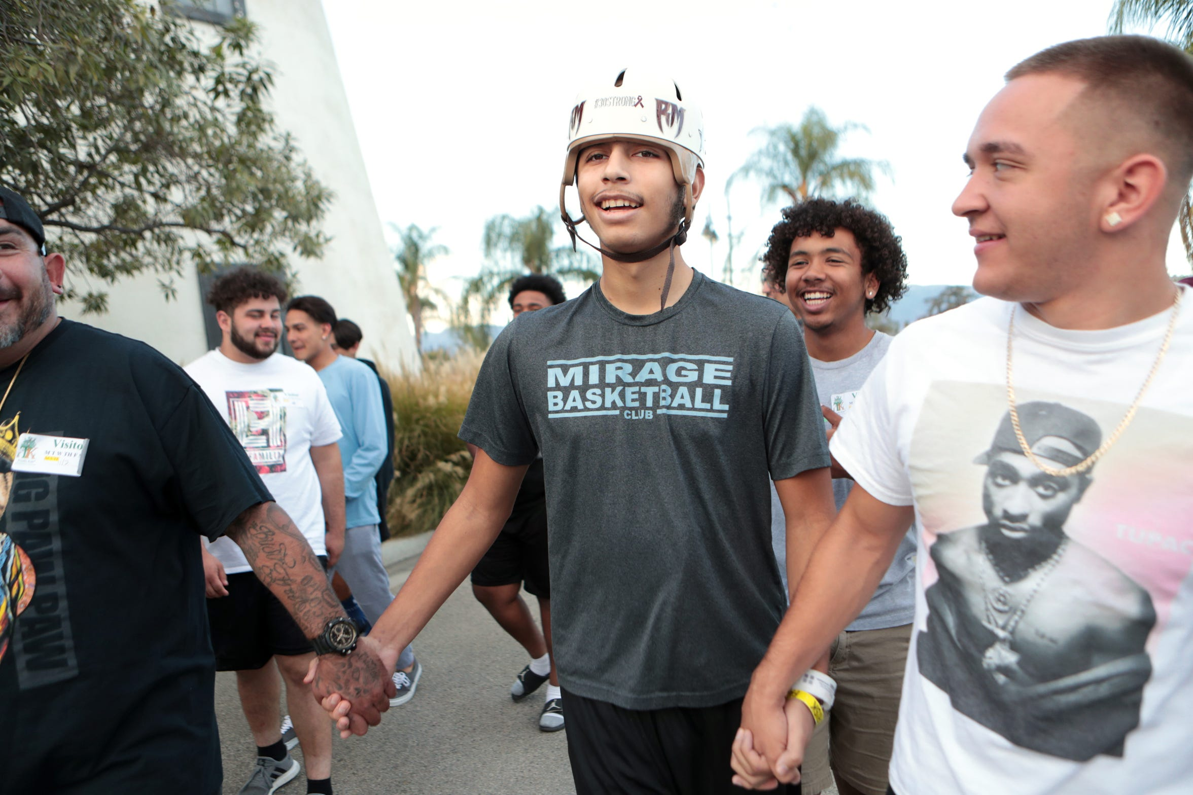 Izzy Ramirez, center, grips the hand of his brother Jessie Alvarez, left, and Joshua Davidson while walking with his Rancho Mirage High School friends and football teammates outside the Totally Kids Rehabilitation Hospital in Loma Linda, Calif., on Saturday, Nov. 2, 2019. Ramirez had a cerebral AVM rupture on Sept. 27, 2019.