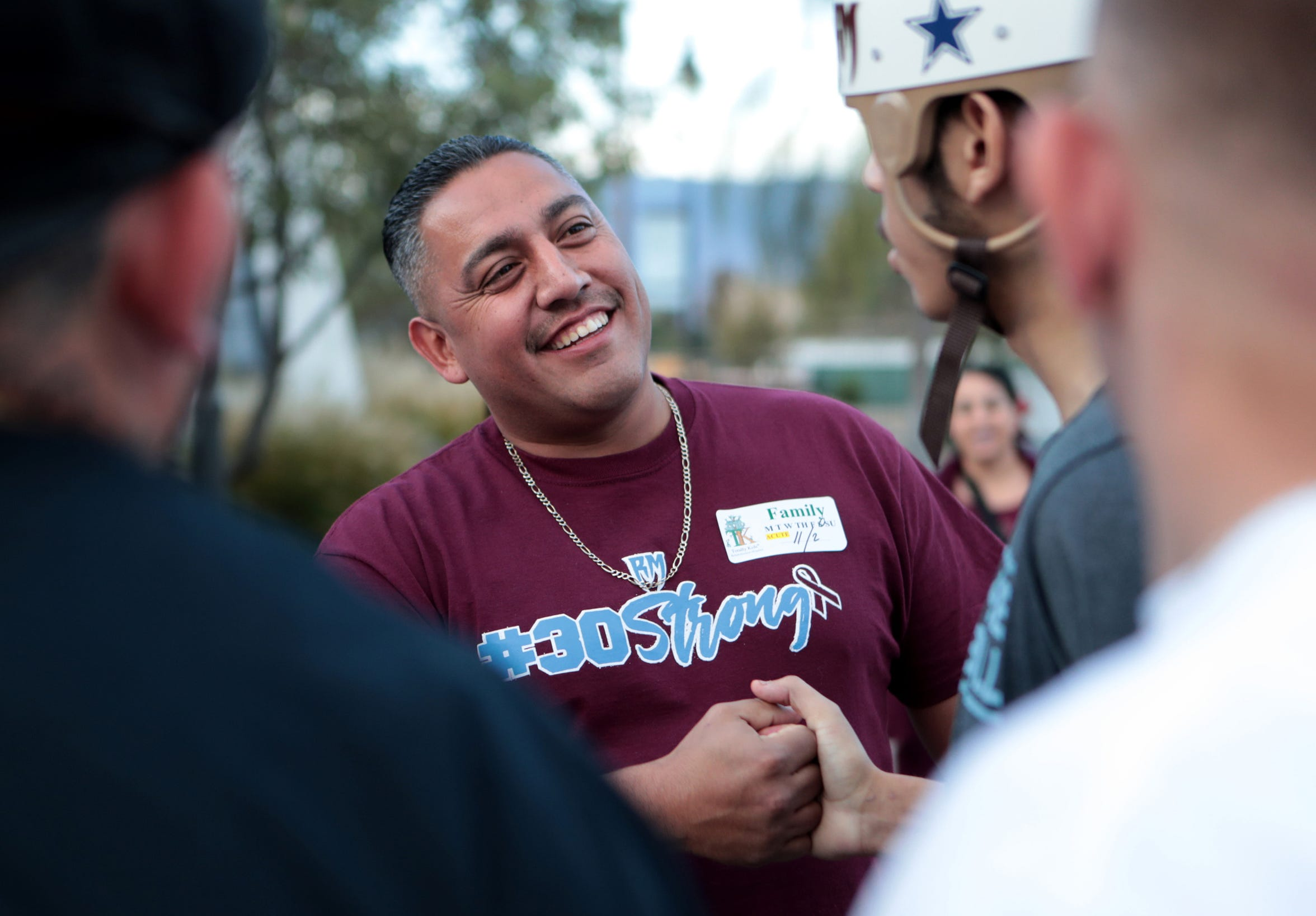 Richard Hernandez, center, smiles as he and Izzy Ramirez talk on Saturday, Nov. 2, 2019, outside the Totally Kids Rehabilitation Hospital in Loma Linda, Calif. On Sept. 27, 2019, Hernandez rushed Izzy to a nearby fire station where emergency personnel provided medical help. Doctors say his urgency saved Izzy's life.