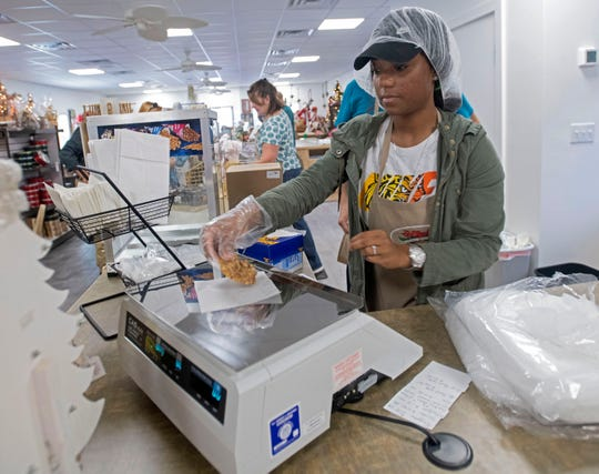 Deashia Hightower weighs a pecan praline for sale at the new J.W. Renfroe Pecan Co. location in downtown Pensacola on Tuesday.