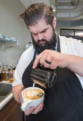 Barista Josh Harden puts the finishing touches on a latte at the new, second location of Constant Coffee & Tea at 11 Palafox Place in downtown Pensacola on Tuesday.