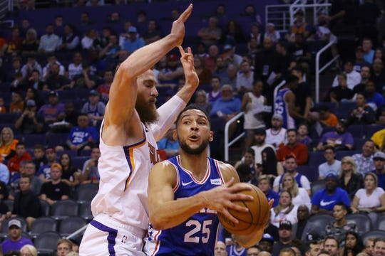 Philadelphia 76ers guard Ben Simmons (25) drives to the basket against Phoenix Suns center Aron Baynes, left, during the first half of an NBA basketball game Monday, Nov. 4, 2019, in Phoenix. (AP Photo/Ross D. Franklin)