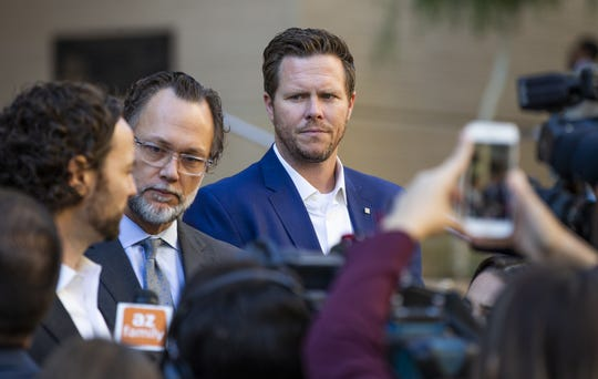 Paul Petersen (upper right) stands on the courthouse steps outside Maricopa County Superior Court on Nov. 5, 2019, after his arraignment. Members of the media interview Petersen's attorneys as he listens.