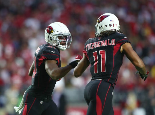 Arizona Cardinals running back Kenyan Drake (41) celebrates with wide receiver Larry Fitzgerald (11) after scoring a touchdown against the San Francisco 49ers in the first quarter at State Farm Stadium.
