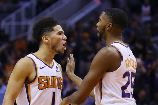 Phoenix Suns guard Devin Booker (1) shouts at Philadelphia 76ers players after scoring and being fouled as teammate Mikal Bridges (25) holds him back during the second half of an NBA basketball game, Monday, Nov. 4, 2019, in Phoenix. The Suns defeated the 76ers 114-109. (AP Photo/Ross D. Franklin)
