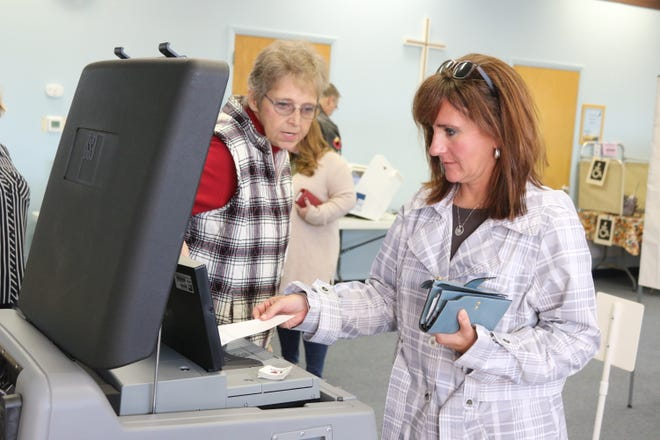 Carrie Sanchez, principal of Port Clinton Middle School, submits her ballot after voting at  Peace Lutheran Church on Tuesday.