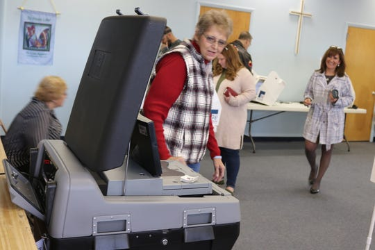Carrie Sanchez, right, principal of Port Clinton Middle School, prepares to submit her ballot after voting at  Peace Lutheran Church on Tuesday.