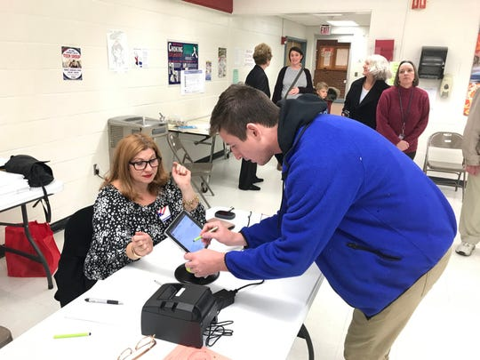 Andrew Dyal of Red Hook, 25, signs in to vote at Red Hook High School as election inspector Amy Pearlman looks on