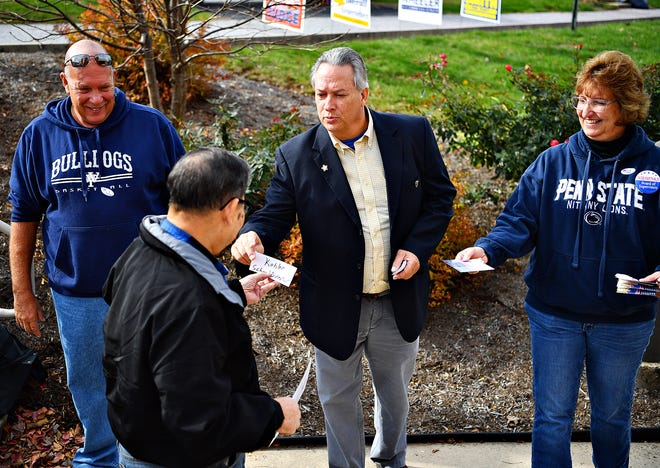 Harry Overlander, left, working the poll for his daughter, West York School Board candidate for Brandy Shope, and Brenda Brown, right, working the poll in support of West Manchester Township supervisor candidate William Niehenke, look on as Lynn Kohler, center, a candidate for West York School Board, greets voters during Election Day at Shiloh Fire Co. in West Manchester Township, Tuesday, Nov. 5, 2019. Dawn J. Sagert photo