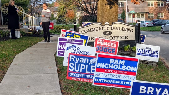 Campaign signs line the street near a polling place in Springettsbury Township as the sun rises on Election Day.