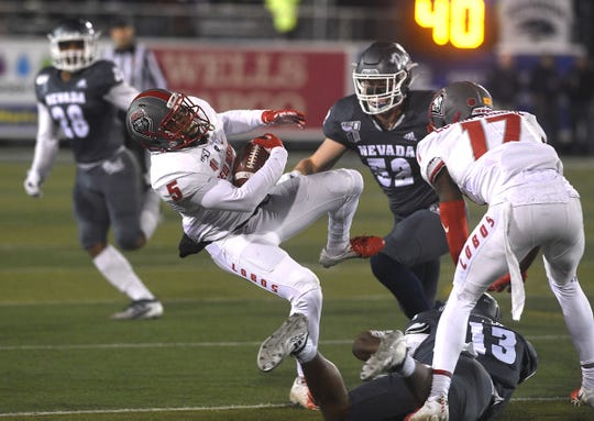 Nevada's Jordan Lee (13) and Kyle Adams (52) defend against New Mexico's Daevon Vigilant (5) during their football game at Mackay Stadium in Reno on Nov. 2, 2019.