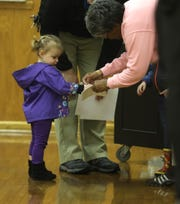 Molly Payne gets a voting sticker from election inspector Thelma Jones. She and her brother, Jim Payne V, had come with their father, Jim Payne IV,  to St. Mary's Ukrainian Orthodox Church in Irondequoit so he could vote.
