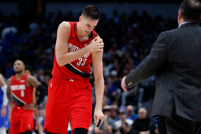 Portland Trail Blazers forward Zach Collins (33) holds his left shoulder as he walks to the bench for assistance after suffering an unknown injury in the second half of an NBA basketball game against the Dallas Mavericks in Dallas, Sunday, Oct. 27, 2019.