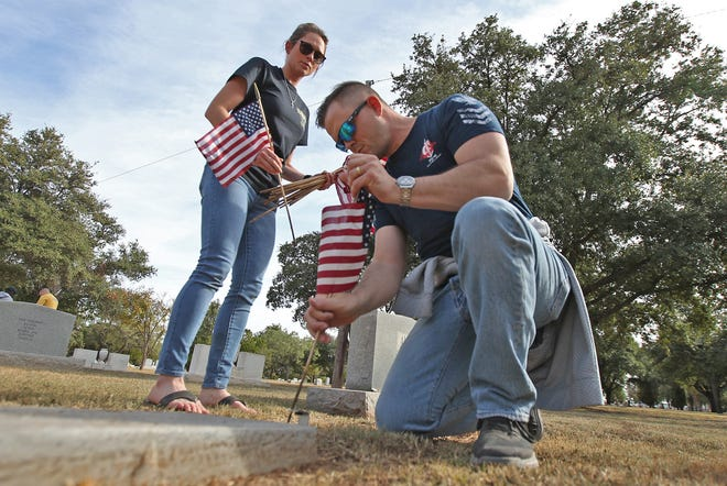 Kelsey Bronkema, left, and Ryan Marriott, right, place a flag at the gravesite of a veteran at Fairmount Cemetery on Sunday, Nov. 3, 2019.