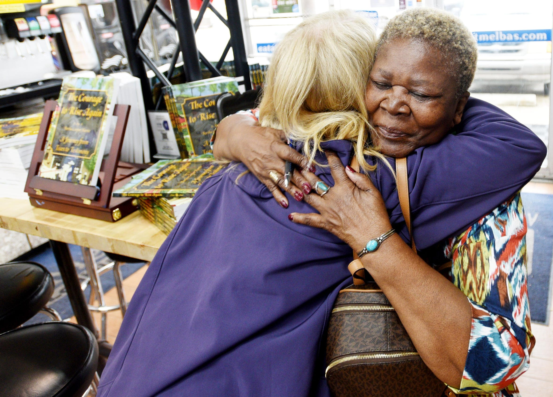 Shreveport author Bertha Harris gets a hug from Lori Newton during the book signing event at Melba's Poboys in New Orleans.