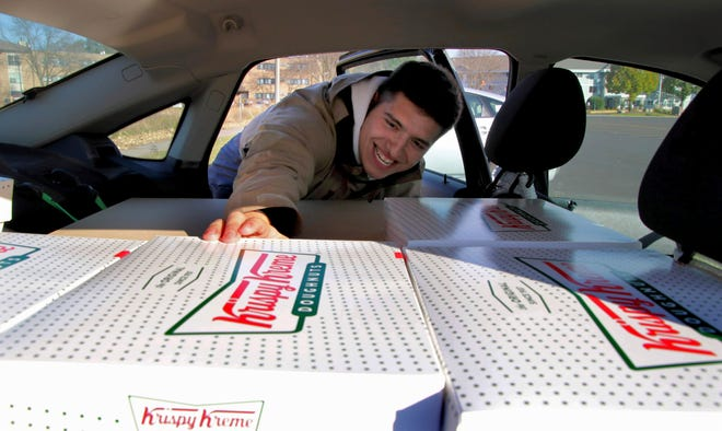 In this Saturday, Oct. 26, 2019 photo, Jayson Gonzalez reaches into his car for another box of Krispy Kreme doughnuts for customers in Little Canada, Minn, who ordered online. Gonzalez, a Minnesota college student, says Krispy Kreme has told him to stop making doughnut runs to Iowa. Gonzalez told the Pioneer Press he was told his sales created a liability for the North Carolina-based company.