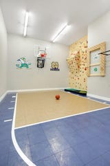 The lower level sport court offers basketball, a full floor-to-ceiling climbing wall, monkey bars and a peg board for the activity enthusiast.