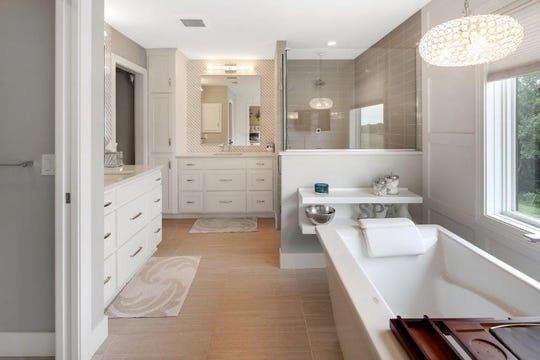The en suite evokes a spa-like atmosphere with a large, contemporary soaking tub set next to a picture window with a delicate chandelier hanging overhead and paneled walls.