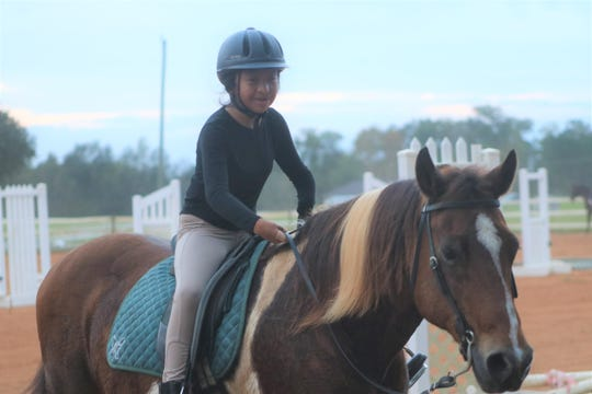 Isabella Tadlock, 11, rides at Butterfly Lane Equestrian Stables Monday, Nov. 4, 2019. Isabella, who was born without hands, is raising money to buy herself a bionic arm.