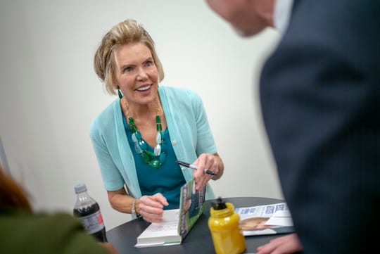 Lesley Visser, a pioneer in sportscasting, autographs her book after the Third Annual Women United Leadership Breakfast at the Turnbull Conference Center.