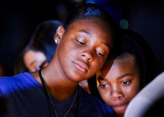 """Tajei Smith (left), 15, and Keasia Johnson, 15, comfort one another during a candlelight vigil in remembrance of Jimarion """"Jay"""" Jones, 14, at Southwest 172nd Avenue on Monday, Nov. 4, 2019, in Indiantown. Jones was shot and killed Sunday night by a 17-year-old friend inside the friend's home in Indiantown. """"He was a very loving and nice person,"""" said Smith."""