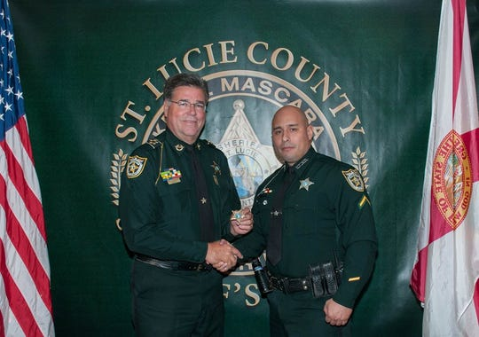 Richard Medina (right), shakes the hand of St. Lucie County Sheriff  Ken Mascara (left), as he was originally promoted to sergeant Aug. 31, 2016, according to a sheriff's office Facebook post.