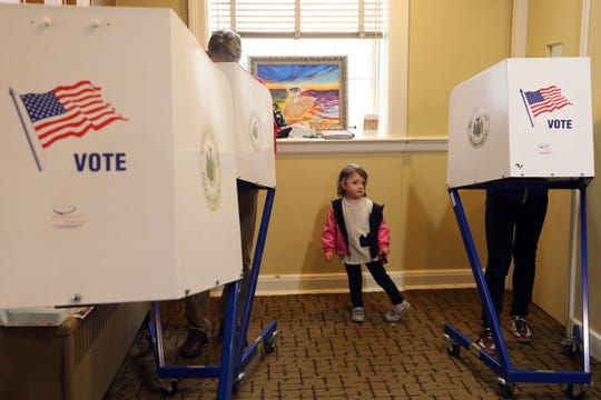 Three-year-old Lillian of South Nyack joins her father Andrew Juhl and mother Sheean Haley as they cast their ballot at Living Christ Church polling station in South Nyack Nov. 5, 2019.