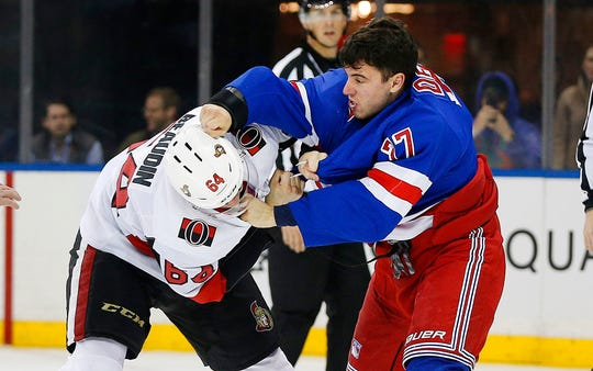 Nov 4, 2019; New York, NY, USA; Ottawa Senators center J.C. Beaudin (64) and New York Rangers defenseman Tony DeAngelo (77) fight during the first period at Madison Square Garden. Mandatory Credit: Andy Marlin-USA TODAY Sports