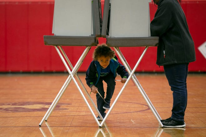 Declan Brady peeks under the voting booth while his grandmother Darlene Walker votes at Drew Middle School on Election Day in Stafford, Virginia on Nov. 5, 2019.