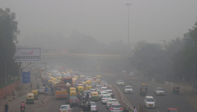 Vehicles wait for a signal at a crossing as New Delhi is enveloped in smog Nov. 3.