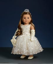 Each of the dolls wear a white ball gown and a Swarovski crystal tiara.