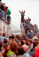 East Germans flood through the dismantled Berlin Wall into West Berlin in 1989.