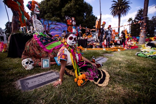 People wearing traditional costumes and make-up stand in front of an altar during the Day of the Dead celebration at the Hollywood Forever Cemetery in Hollywood, Los Angeles, California, Nov. 2, 2019.
