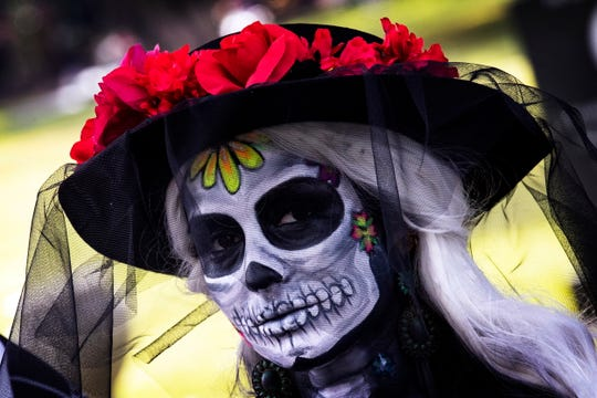 A visitor wearing a costume attends the Day of the Dead celebration at the Hollywood Forever Cemetery