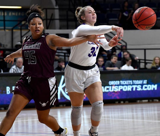 McMurry University's Abrelle Godfrey reaches for the ball as ACU's Makayla Mabry passes during Tuesday's match at Abilene Christian University.